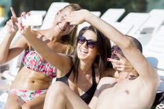 Beaux jeunes amis riant et faisant le selfie sur la piscine Photographie stock libre de droits