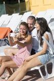 Beaux jeunes amis riant et faisant le selfie sur la piscine Photos stock