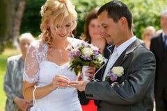 Beaux jeunes anneaux de mariage d'échange de couples de mariage Images stock