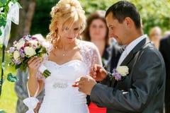 Beaux jeunes anneaux de mariage d'échange de couples de mariage Photos libres de droits