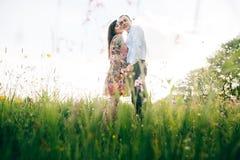 Beaux jeunes couples étreignant doucement en soleil dans le pré frais de ressort avec les fleurs roses Famille élégante heureuse  photo stock