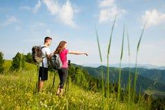 Beaux jeunes couples actifs augmentant la colline s'élevante de nature d'ina ou Image libre de droits