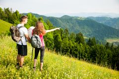 Beaux jeunes couples actifs augmentant la colline s'élevante de nature d'ina ou Image stock
