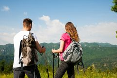 Beaux jeunes couples actifs augmentant la colline s'élevante de nature d'ina ou Photos stock