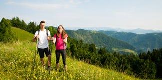 Beaux jeunes couples actifs augmentant la colline s'élevante de nature d'ina ou photographie stock libre de droits