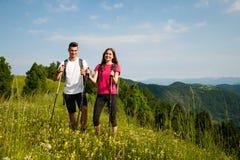 Beaux jeunes couples actifs augmentant la colline s'élevante de nature d'ina ou Photographie stock