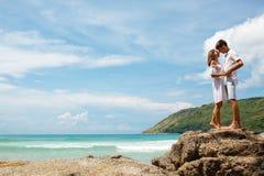 Beaux jeunes couples adultes se tenant sur les roches Photos stock