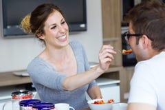 Beaux jeunes couples appréciant le petit déjeuner dans la cuisine à la maison Photos libres de droits