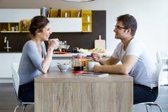 Beaux jeunes couples appréciant le petit déjeuner dans la cuisine à la maison Photos stock