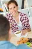 Beaux jeunes couples appréciant le petit déjeuner dans leur nouvelle maison Photos stock