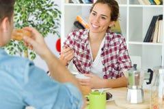 Beaux jeunes couples appréciant le petit déjeuner dans leur nouvelle maison Images libres de droits