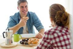 Beaux jeunes couples appréciant le petit déjeuner dans leur nouvelle maison Photos libres de droits