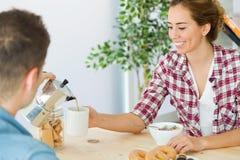 Beaux jeunes couples appréciant le petit déjeuner dans leur nouvelle maison Photo stock