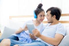 Beaux jeunes couples asiatiques écoutant la musique avec le comprimé sur la chambre à coucher Image stock