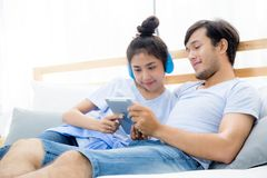 Beaux jeunes couples asiatiques écoutant la musique avec le comprimé sur le lit Photo libre de droits