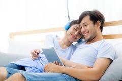 Beaux jeunes couples asiatiques écoutant la musique avec le comprimé sur le lit Photos libres de droits