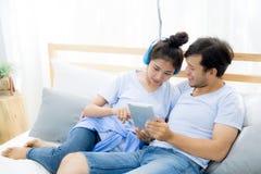 Beaux jeunes couples asiatiques écoutant la musique avec le comprimé sur le lit Images stock