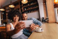 Beaux jeunes couples au café prenant le selfie avec le téléphone portable Images libres de droits