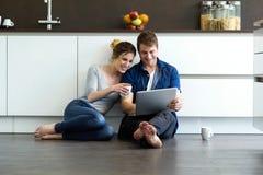 Beaux jeunes couples au moyen de eux comprimé numérique dans la cuisine Photographie stock libre de droits