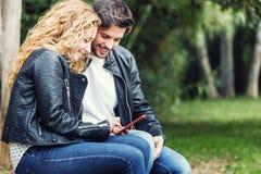 Beaux jeunes couples au moyen de eux téléphone portable en parc Image libre de droits