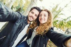 Beaux jeunes couples au moyen de eux téléphone portable en parc Photo libre de droits