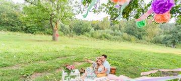 Beaux jeunes couples ayant le pique-nique dans la campagne Famille heureuse extérieure Homme et femme de sourire détendant en par photographie stock