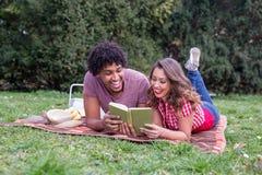 Beaux jeunes couples ayant le pique-nique heureux au sujet du beau temps au sujet de photo libre de droits