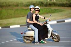 Beaux jeunes couples d'amour sur le scooter Images libres de droits