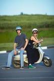 Beaux jeunes couples d'amour sur le scooter Image stock