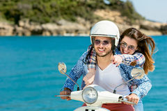 Beaux jeunes couples dans l'amour appréciant et ayant l'équitation d'amusement sur un scooter dans une belle nature Photo stock