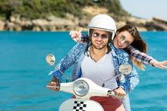 Beaux jeunes couples dans l'amour appréciant et ayant l'équitation d'amusement sur un scooter dans une belle nature Photos stock