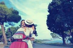 Beaux jeunes couples dans l'amour appréciant et ayant l'équitation d'amusement sur un scooter Images stock