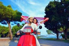 Beaux jeunes couples dans l'amour appréciant et ayant l'équitation d'amusement sur un scooter Images libres de droits