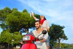 Beaux jeunes couples dans l'amour appréciant et ayant l'équitation d'amusement sur un scooter Image libre de droits
