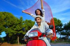 Beaux jeunes couples dans l'amour appréciant et ayant l'équitation d'amusement sur un scooter Photos libres de droits