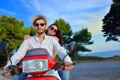 Beaux jeunes couples dans l'amour appréciant et ayant l'équitation d'amusement sur un scooter Photos stock