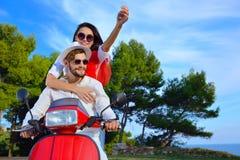 Beaux jeunes couples dans l'amour appréciant et ayant l'équitation d'amusement sur un scooter Photographie stock