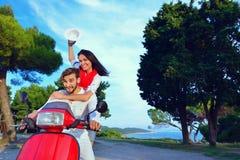 Beaux jeunes couples dans l'amour appréciant et ayant l'équitation d'amusement sur un scooter Photographie stock libre de droits
