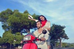 Beaux jeunes couples dans l'amour appréciant et ayant l'équitation d'amusement sur un scooter Image stock