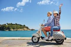 Beaux jeunes couples dans l'amour appréciant et ayant l'équitation d'amusement sur un scooter dans une belle nature Images stock
