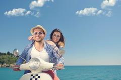 Beaux jeunes couples dans l'amour appréciant et ayant l'équitation d'amusement sur un scooter dans une belle nature Photographie stock