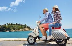 Beaux jeunes couples dans l'amour appréciant et ayant l'équitation d'amusement sur un scooter dans une belle nature Photographie stock libre de droits