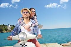 Beaux jeunes couples dans l'amour appréciant et ayant l'équitation d'amusement sur un scooter dans une belle nature Photo libre de droits