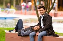 Beaux jeunes couples dans l'amour dans le jour de valentines de St, femme couchée dans des ses jambes d'ami, en parc Image libre de droits