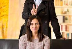 Beaux jeunes couples dans l'amour dans le jour de valentines de St, homme faisant un signe au-dessus de sa tête d'amie à un arriè Photographie stock