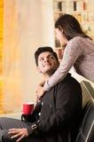 Beaux jeunes couples dans l'amour dans le jour de valentines de St, homme tenant une tasse rouge à un arrière-plan brouillé de bu Photo stock