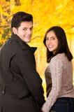 Beaux jeunes couples dans l'amour dans le jour de valentines de St tenant leurs mains à un arrière-plan brouillé de parc d'autum Image stock