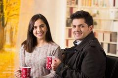 Beaux jeunes couples dans l'amour dans le jour de valentines de St, tenant une tasse de coffe à un arrière-plan brouillé Photographie stock libre de droits