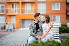 Beaux jeunes couples dans l'amour en parc sur un banc Belle femme avec de longs cheveux sombres et un homme étreignant dans la ru Photographie stock