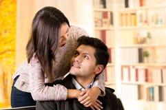 Beaux jeunes couples dans l'amour, femme embrassant son ami à un arrière-plan de bureau Photographie stock